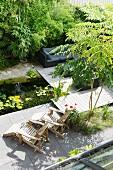 Gartenteich, Holzliegestühle und Lounge neben Bambus auf Holzterrasse