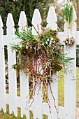 Spring wreath made of snowdrops, moss and willow catkins hung on white picket fence