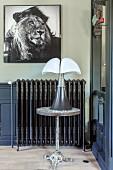 Bild mit Löwenmotiv über verziertem Heizkörper, davor Beistelltisch und Tischleuchte