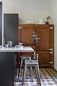 Marmor-Thekenplatte und Klassiker Barhocker auf Ornamentfliesenboden in der Küche