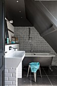 Free-standing bathtub against mosaic-tiled wall below grey sloping ceiling