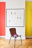 Stuhl mit Lederbezug und Bücherstapel vor Kunstobjekt und farbiger Wandgestaltung