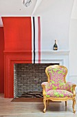 Antique armchair with neon upholstery in front of traditional fireplace painted with red, white and black stripes