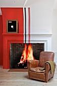 Vintage Ledersessel vor Kamin mit Feuer und rotem Anstrich