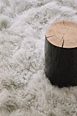 Side table made from black-painted tree stump on fluffy rug