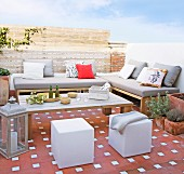 Terracotta tiles, upholstered outdoor furniture and cubic pouffes on summery terrace