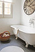 Free-standing bathtub and large vintage clock in bathroom