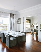 Grey loose-covered chairs around white dining table below window in elegant dining room with sliding door