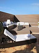 Elegant lounger and benches with cushions on sunny roof terrace