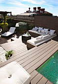 Elegant lounger and benches with white cushions on sunny roof terrace with pool