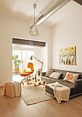Black leather couch and DIY pallet table on cream rug in front of orange armchair