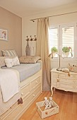 Bed with drawers below and vintage-style bedside cabinet