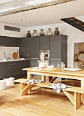 Wooden table and benched on oak parquet floor in front of grey kitchen