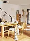 Writing utensils on wooden table and wooden chairs in front of slim balustrade on staircase and tree-shaped coat stand