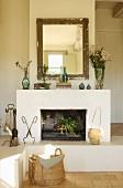 Gilt-framed mirror above open fireplace on masonry plinth