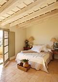 Wood-beamed ceiling and terracotta floor in Mediterranean bedroom