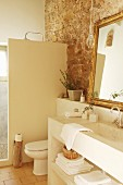 Exposed stone wall and masonry furnishings in rustic bathroom