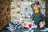 Feathers and antique dolls in box with sides covered in torn paper