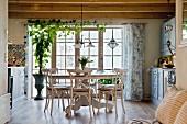 Gemütlicher Essplatz mit rundem Tisch und rustikaler Holzbalkendecke