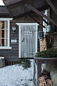 Swedish wooden house with snow and fir branches outside front door