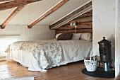 Rustikales Schlafzimmer unter dem Dach mit Holzbalken und Ofen