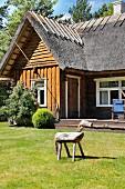 Holzpferd steht auf dem Rasen vor einem Holzhaus mit Strohdach