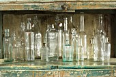 Various glass bottles in rustic kitchen cupboard