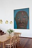 Eleganter Esstisch mit Stühlen, Pendelleuchten und moderne Kunst im Hintergrund
