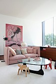 Children's chairs around glass coffee table and dusky-pink couch with scatter cushions in elegant lounge