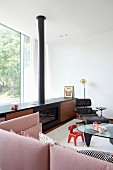 Sideboard with integrated fireplace, Eames Lounge Chair, children's chairs around glass coffee table and dusky-pink couch in elegant lounge