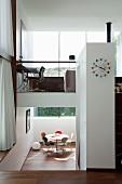 Runder Tisch mit Klassikerstühlen im Untergeschoss, darüber Home Office in elegantem Architektenhaus