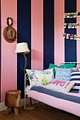 Colourful scatter cushions on couch against wall with wide pink and blue stripes