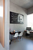White classic chairs and picture of Albert Einstein in study in concrete house