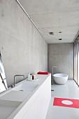 Minimalistisches Designerbad in Betonhaus mit weißer, freistehender Badewanne und rotem Farbakzent