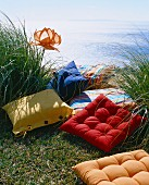 Colourful cushions on grass next to the sea