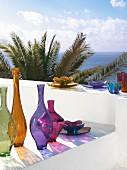 Bunte Glasvasen und Schalen auf einer weißen Mauer am Meer