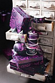 Purple boxes and silk ribbons on and in chest of small drawers