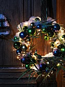 Christmas wreath with peacock figurine, feathers and fairy lights