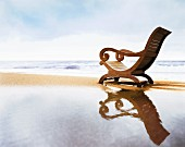 Lounger with curved backrest on beach