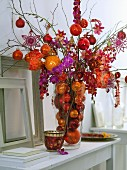 Christmas arrangement of orchids and baubles in shades of red, orange and purple