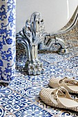 Claw foot of bathtub on blue and white patterned floor tiles