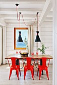 Red metal chairs around wooden table in white wooden house
