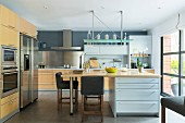 Elegant fitted kitchen with dining table extension on island counter