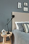 Black lamp on bedside table next to bed with beige headboard and grey cover against grey wall