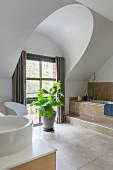 Elegantes Badezimmer mit Steinfliesen, Badewanne und Zimmerpflanze vor dem Fenster