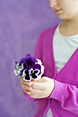 Child holding posy of violas