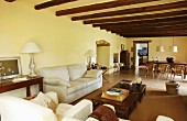 Offener Wohnbereich mit Loungemöbeln und Holzbalkendecke in renoviertem Landhaus