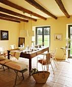 Armlehnstühle und Bank um Schubladentisch in mediterranem Essbereich mit Holzbalkendecke