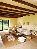 White sofa, floor cushions, side table and wood-beamed ceiling in comfortable lounge area of renovated country house