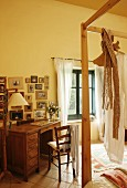 Vintage desk and wooden chair below gallery of pictures in country-house bedroom